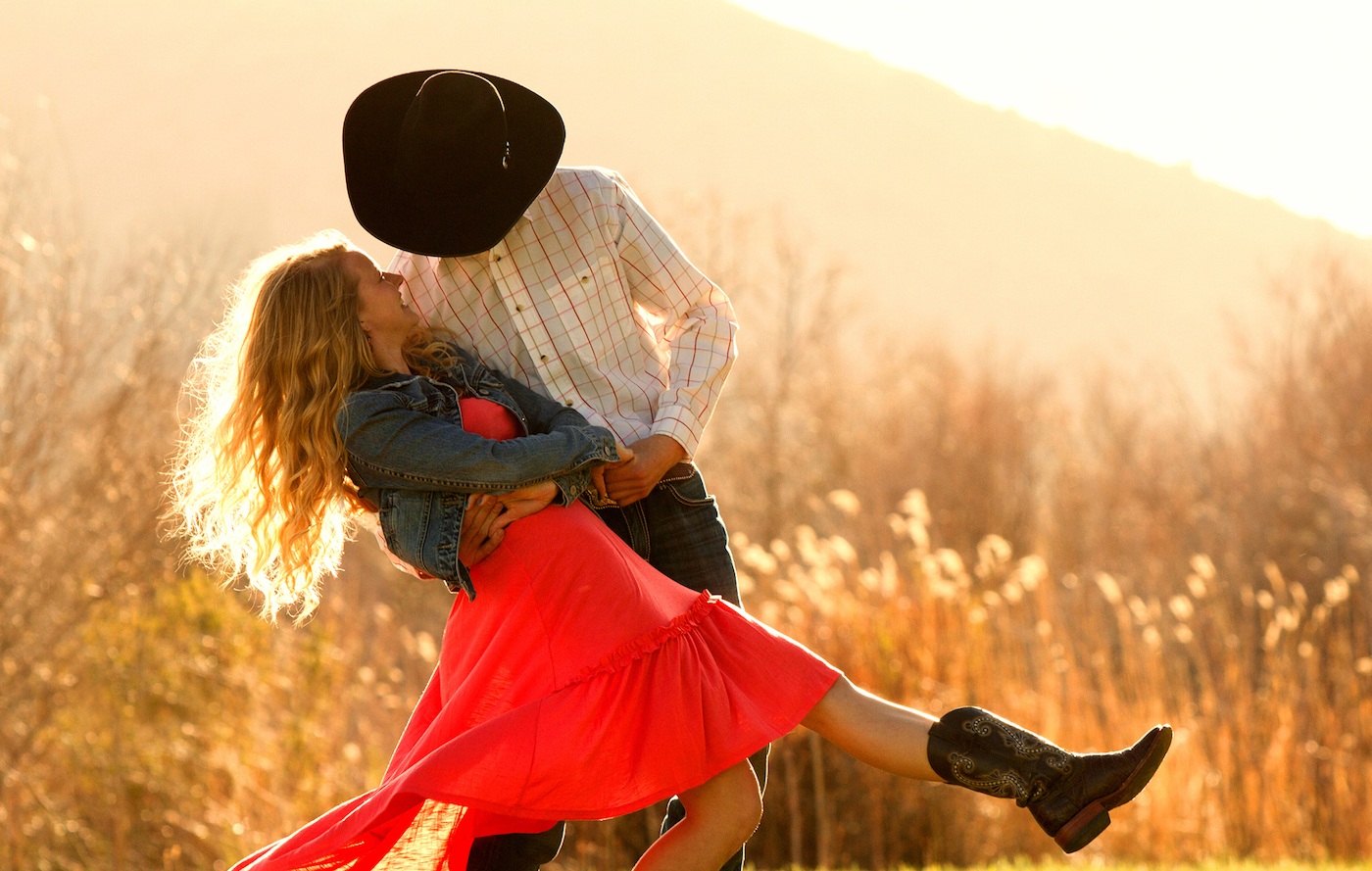 Cowboy dancing with a cute cowgirl in a pasture