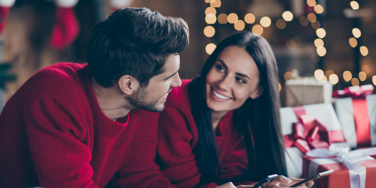Close up photo of two romantic married people use cell phone feel romance, lying on floor with gift boxes have christmas vacation x-mas holidays in house indoors
